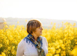 idős hölgy egy sárga virágos réten